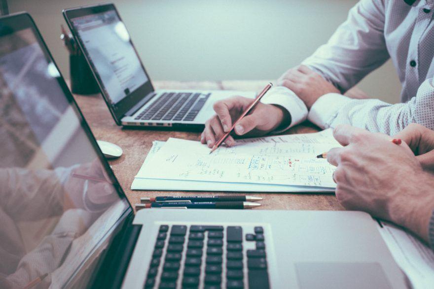 Zwei Menschen entwerfen ein Dokument zwischen zwei Computern.