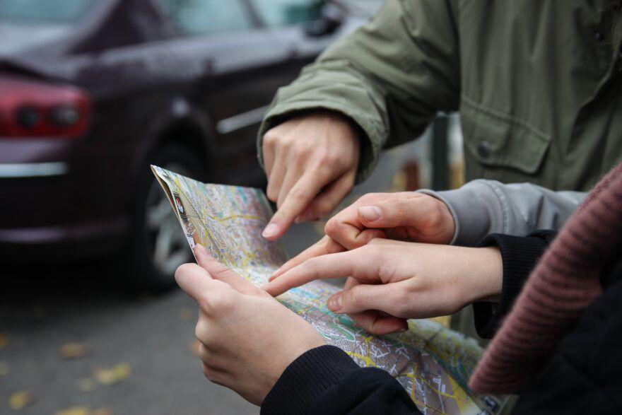 Menschen zeigen mit Fingern auf eine Landkarte.